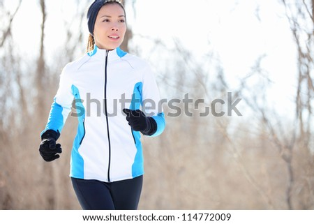 Running young Asian woman jogging in a winter fleece and gloves in open countryside with copyspace in a health and fitness concept