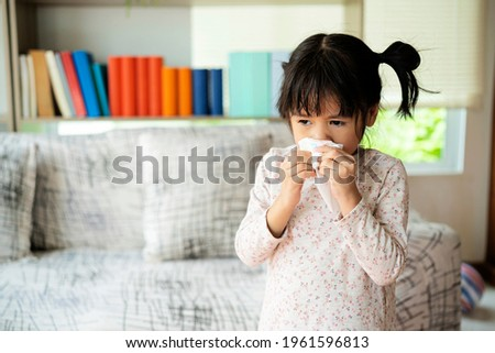 Runny nose. Sick little girl blowing her nose and covering it with handkerchief Stock photo ©