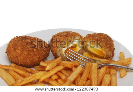 Runny yolk Scotch eggs and chips with a fork on a plate