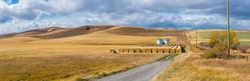 Rural Alberta Canadian prairie grassland landscape countryside background panorama. Beautiful farmer's field and grain silos with hay bales wallpaper
