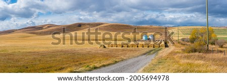 Rural Alberta Canadian prairie grassland landscape countryside background panorama. Beautiful farmer's field and grain silos with hay bales wallpaper  Photo stock ©