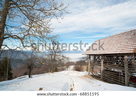 Rural Alpine view of typical Slovenian shed on mountains background under blue sky near hiking trail in snow.