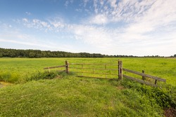 Rural area with green grassland and in the foreground a rusty iron gate between two wooden beams and closed with a chain and padlock.