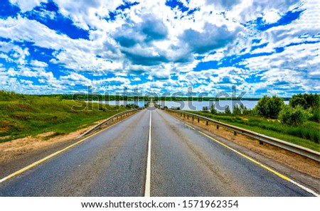 Rural asphalt road under cloudy sky. Rural river road landscape. Cloudy sky over rural road. Rural road sky clouds landscape