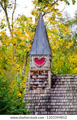 Rural church steeple in Autumn. A vintage wooden steeple with a red heart sits among trees with leaves changing to  rich yellow color
