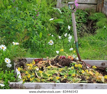 Rural compost pile with a rustic pitch fork and flowers in the background #83446543