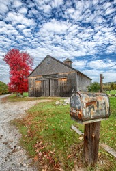 Rural country scene with rusting mailbox, barn, red fall foliage, and dramatic clouds