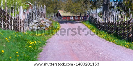 Rural countryside summer idyll - Green grass Yellow flowers beside road and wooden fence leading to small idyllic Swedish village Åsens by Småland. #1400201153