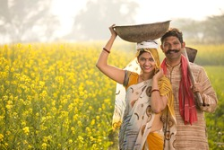 Rural couple with iron pan and hoe in agricultural field
