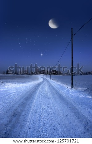 Rural dirt road in winter evening with half moon and stars in sky
