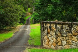 Rural driveway entrance with winding country road and sandstone wall surrounded by trees