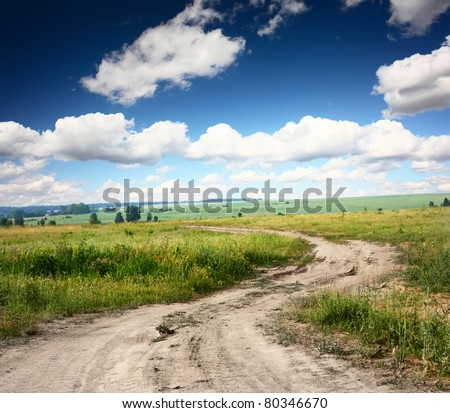 Rural dusty countryside road trough a fields with wild herbs and flowers