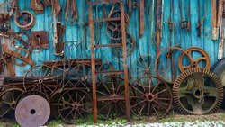 Rural farm house wall used as a waste disposal decoration with old, rusty and rotten agricultural tools. Agriculture concept. Texture and background for text.