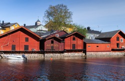 Rural Finnish landscape. Traditional old red wooden houses and barns are on the river coast, historical part of Porvoo town, Finland