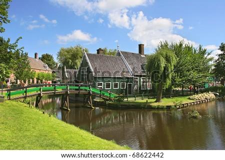 Rural house and bridge over small creek in Zaanse Schans village, Netherlands (Holland).