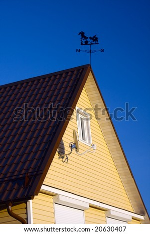 Rural house roof with satellite antenna on a wall and windrose. Clear deep blue sky backdrop. Sunny day.