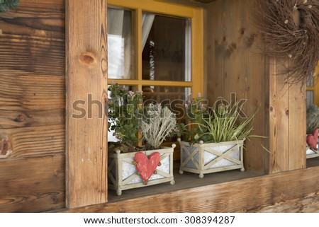 rural house with flowers on a wooden window sill