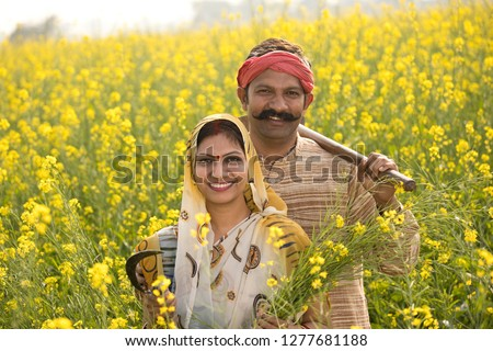 Rural Indian couple farming in agricultural field #1277681188