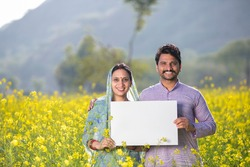 Rural Indian couple in rapeseed field
