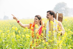 Rural Indian couple in rapeseed field with agricultural work tool