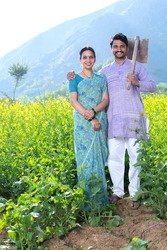 Rural Indian couple standing in rapeseed field at village