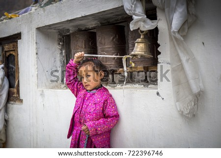 rural indian girl child is playing with prayer bells in a chorten near kaza, himachal pradesh, india