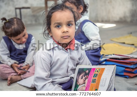 Rural Indian Pre school Kids sitting on the floor of their classroom.