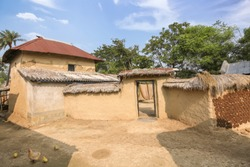 Rural Indian village at Bolpur West Bengal with view of mud hut with cow dung on the wall used as fuel and hen with chicks on the courtyard