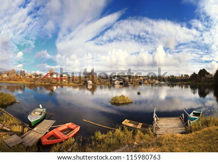 rural landscape at the river, wooden boats, water, blue sky