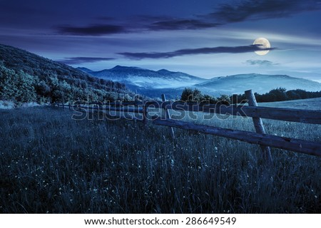 rural landscape. fence on the hillside meadow shot with ultrawideangle lense. forest in fog on the mountain top at night in full moon light