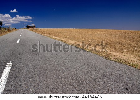 Rural landscape of the Portuguese northeast seeing, empty road, rye fields after crop and hut against deep blue sky and white clouds