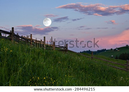 Rural landscape with a full moon at sunset