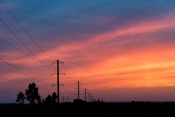 Rural landscape with power poles at sunrise