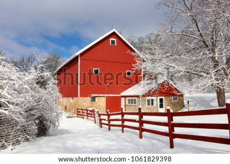 Rural landscape with red barn, wooden red fence and trees covered by fresh snow in sunlight. Scenic winter view at Wisconsin, Midwest USA, Madison area.Agriculture and rural life at winter background.