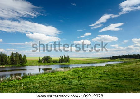 Rural landscape with river flowing among green meadows with trees with blue cloudy sky on the background
