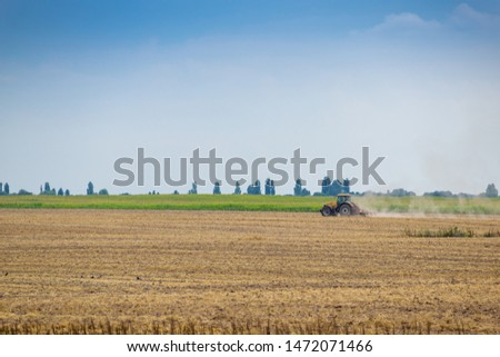 Rural landscape with tractor cultivating the field