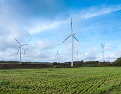 rural landscape with wind turbines and freshly mown grass under blue cloudy sky in german eifel during fall