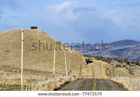 Rural Montana Scene with a Tractor on a Hill and a Paved Road that turns to dirt.