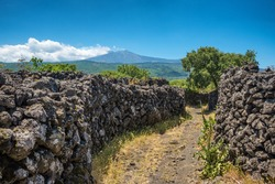 Rural road along old lava stone wall with Etna volcano view in Sicily, Italy
