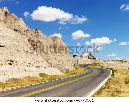 Rural road by rock formations and a field in Badlands National Park, South Dakota. Horizontal shot.