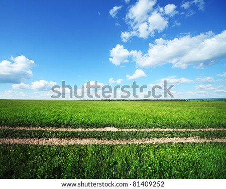 Rural road in green meadow and blue sky with clouds - stock photo