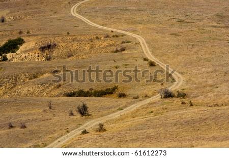 rural road on desert land - stock photo