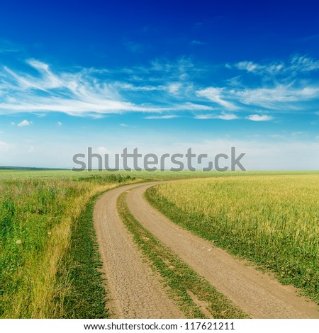rural road to horizon under cloudy sky - stock photo