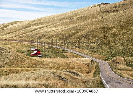 Rural road with red barns and lots of fences.  The fence climbing the largest hill looks like tiny stitches.