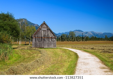 Rural road with wooden house and countryside landscape near Wolfgangsee lake, Austria