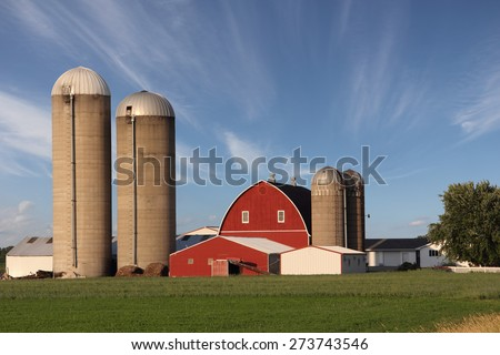 Rural scene showing a modern family farm with a bright red barn surrounded by silos.  Dramatic blue sky with wispy clouds.  The sky also provides text space if needed.