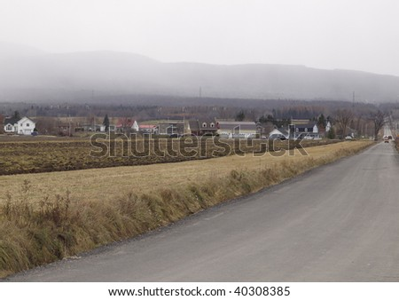 rural scene with building and mountain in the background. Fog and cloudy bad weather.