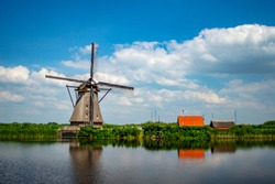 Rural scene with traditional Dutch windmill and houses at Kinderdijk, Netherlands.