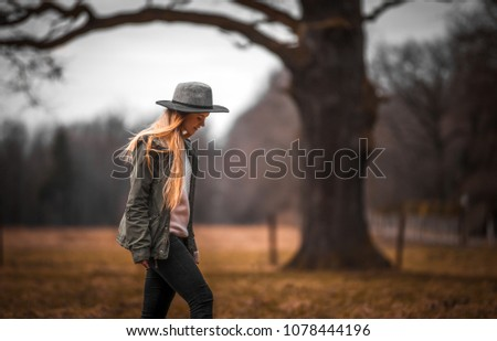 Rural scene with woman in hat walking on field, melancholic autumn mood #1078444196