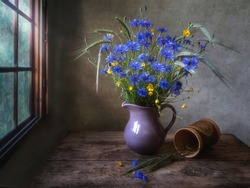 Rural still life with bouquet of cornflowers